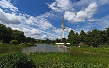 Hamburger Fernsehturm hinter Park und Wasser, vor blauem Himmel