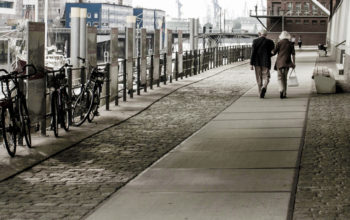 Rückansicht eines Paares aus der Entfernung, das in der Hamburger HafenCity spazieren geht